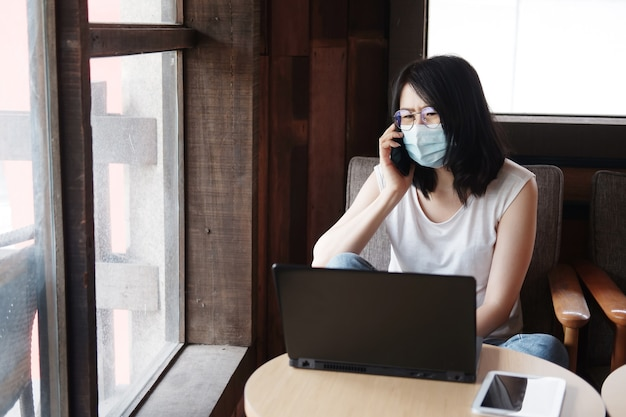 Азиатская женщина носит маску для предотвращения covid-19 и звонит на смартфон. деловая женщина работает в сети с ноутбуком в гостиной. работа на дому в рамках концепции вспышки corona visus.