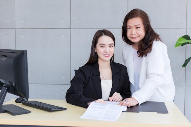 아시아 여성이 사무실에서 상사와 논의하기 위해 종이나 문서를 가리키며 일하고 있습니다.