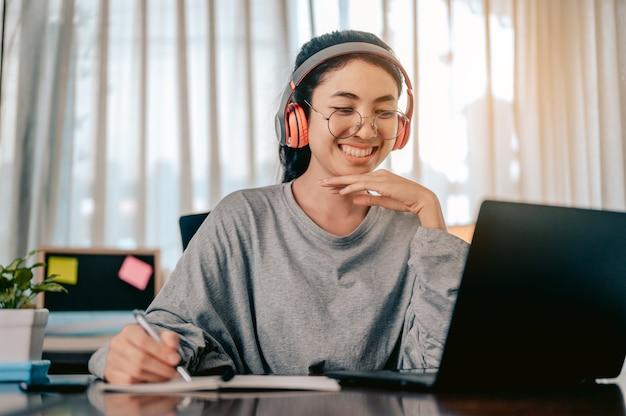 アジアの女性は音楽を聴いているヘッドフォンを身に着けている自宅のリビングルームで働いています