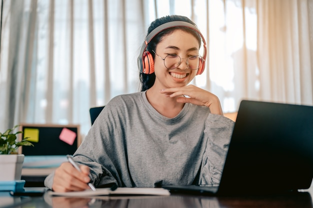 Asian woman is working in the living room at home wearing headphones listening to music