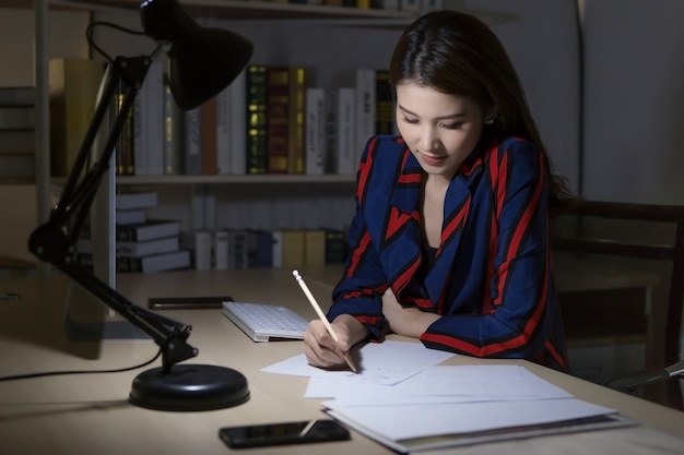 An asian woman is writing work into the paper which it put on the desk in the office room at night.