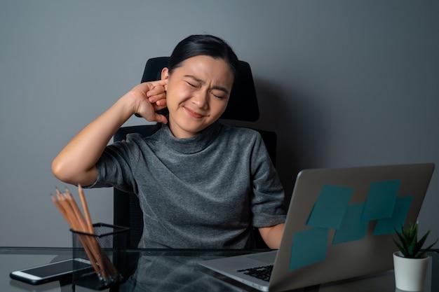아시아 여자 가려움증과 그녀의 귀에 손가락을 넣어 사무실에서 노트북에서 작업