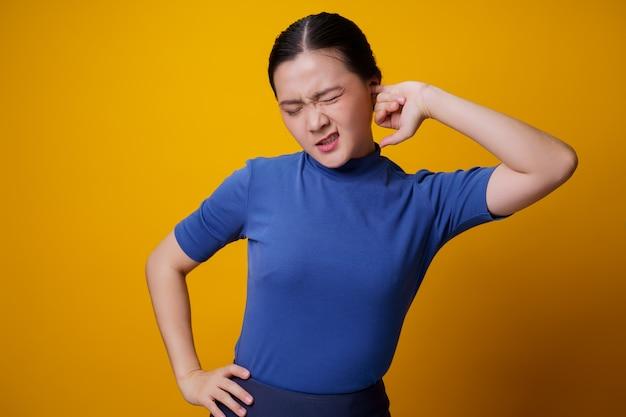 黄色の上に立っている彼女の耳にかゆみと指を入れているアジアの女性。