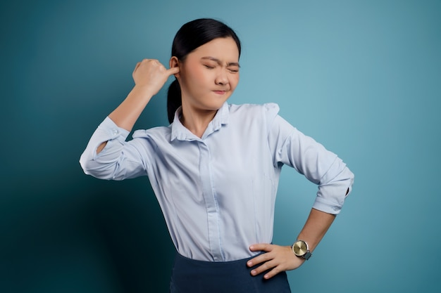 Asian woman itching and putting a finger into her ears standing isolated on blue.