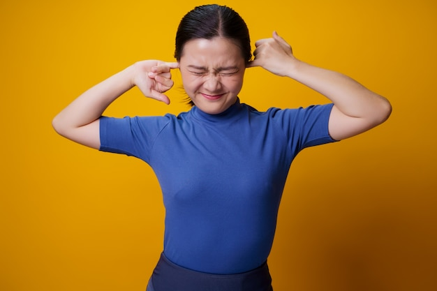 Asian woman itching and putting a finger into her ears standing over yellow.