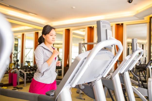 피트니스 체육관 방 안에서 조깅하는 아시아 여성.
