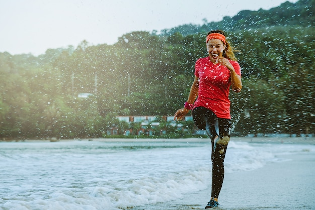 Asian woman jogging workout on the beach in the morning.