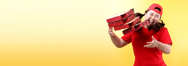 Asian woman jumped glad in red cap, giving food order italian pizza in cardboard boxes isolated