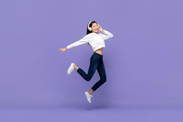 아시아 여자 점프와 헤드폰에서 음악을 듣고