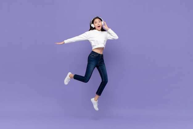 Asian woman jumping and listening to music on headphones
