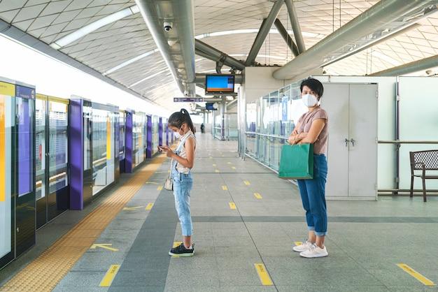 아시아 여자는 빈 지하철 플랫폼에서 다른 사람들과 거리를 유지