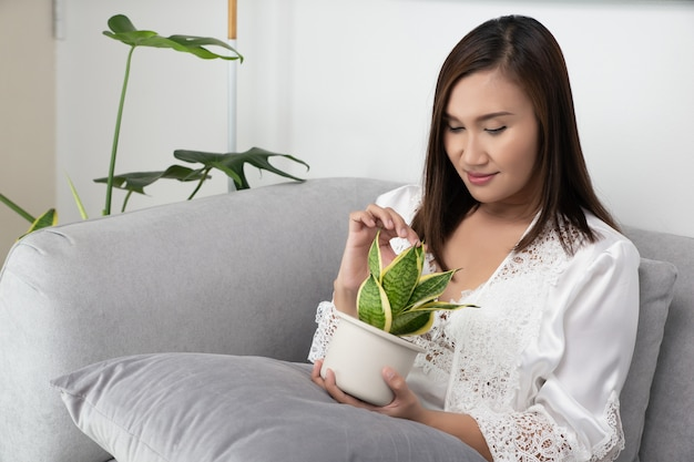 Asian woman in lace white nightwear and silk robe holds plants sitting on the gray sofa
