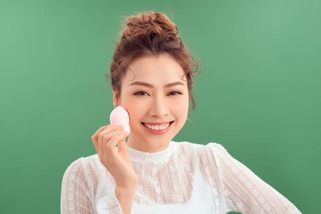 Азиатская женщина смеется и держит губку для лица, изолированную на зеленом фоне