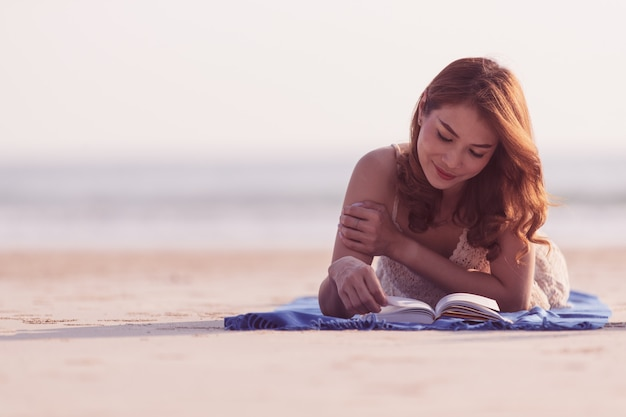Asian woman laying down on beach and reading