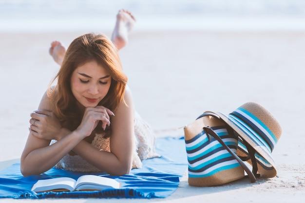 Азиатская женщина, лежа на пляже и чтения