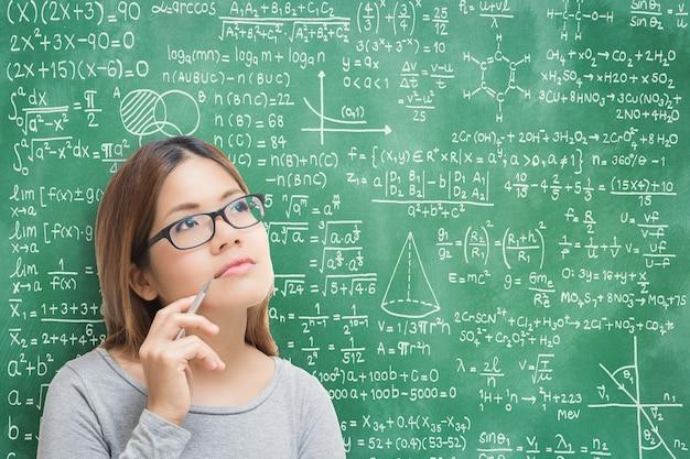 Азиатская женщина учится или решает проблему с фоном доски