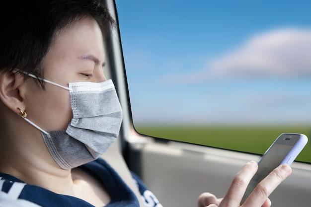 아시아 여성 lgbt는 코로나 바이러스 코비드 19 팬더믹에서 사회적 검역을 위해 셀로혼 스마트폰을 사용하는 새로운 도덕적 생활 방식을 위해 차에서 마스크를 보호합니다.