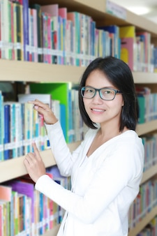 Asian woman in library selecting book to read