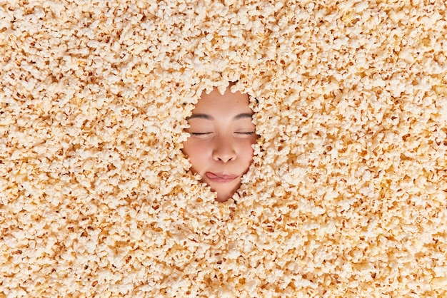 Asian woman licks lips keeps eyes closed imagines eating appetizing snack drowned in delicious sweet popcorn going to watch movie with friends. overhead shot. yummy air popped corn