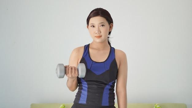 家に立っている間半腕のバーベルを持ち上げるアジアの女性