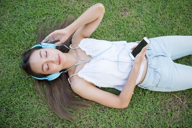 アジアの女性が芝生で音楽を聴く