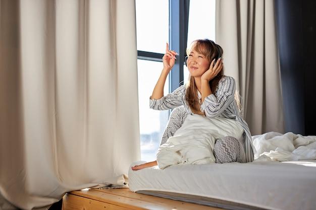 Азиатская женщина слушает музыку в наушниках, сидя на кровати в пижаме, расслабляется на досуге, дома