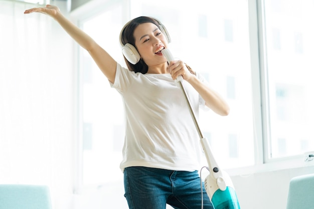 Asian woman listening to music and dancing with a vacuum cleaner