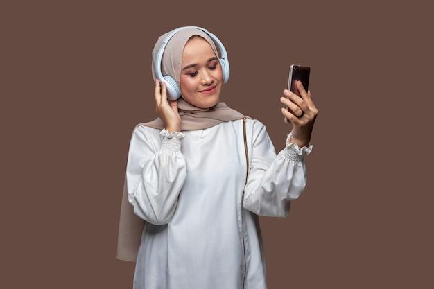 彼女の目を閉じている間ワイヤレスヘッドフォンを使用して携帯電話から音楽を聞いているアジアの女性