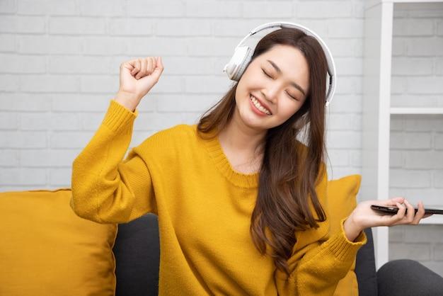 Азиатская женщина слушает музыку в наушниках и сидит на диване в комнате дома