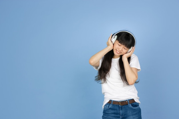 Asian woman listening to music with headphones on blue