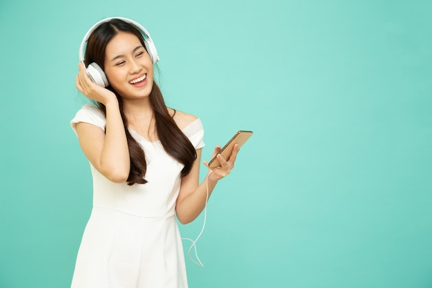 Asian woman listening music with headphones on mobile phone isolated on green background