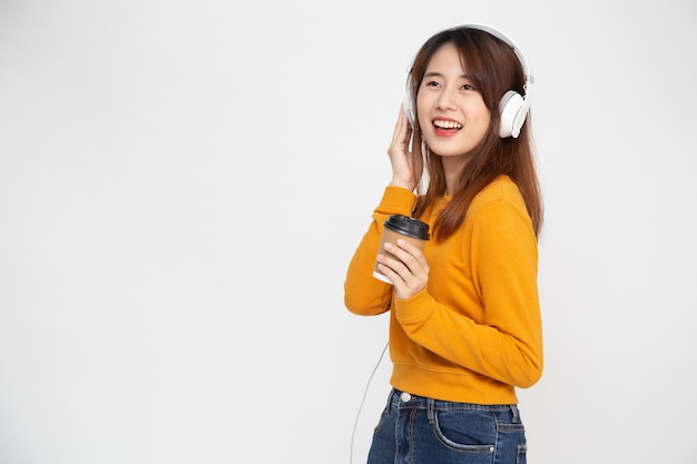 Азиатская женщина слушает музыку в наушниках на изолированной на белой стене