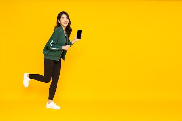 노란색 배경에 격리된 전화기에서 무선 이어폰으로 음악을 듣는 아시아 여성