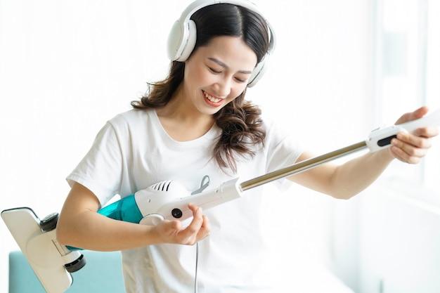 音楽を聴き、掃除機で踊るアジアの女性