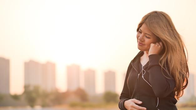 일몰 하늘을 배경으로 음악을 듣는 아시아 여성