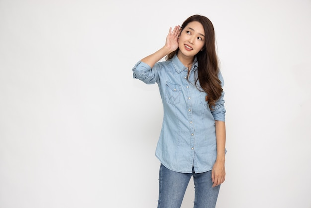 Азиатская женщина слушает что-то, положив руку на ухо, изолированное на белом фоне