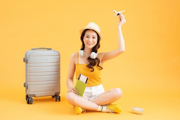 アジアの女性の長い髪はパスポートの本と旅行バッグを持って手に麦わら帽子を着用します