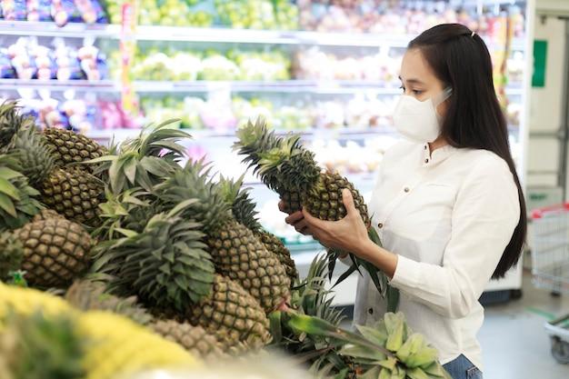 スーパーマーケットのデパートで保護フェイスマスクを身に着けているアジアの女性の長い髪