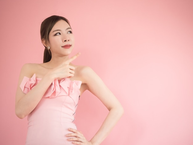 Asian woman look up and pointing up, beautiful women posing on pink background.