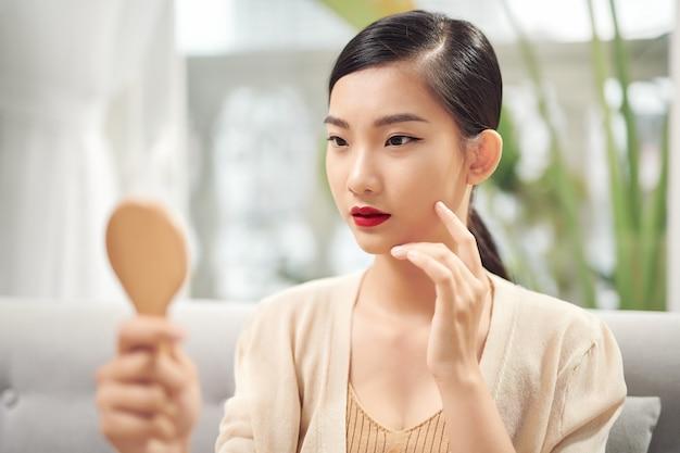 거울에 비친 자신의 얼굴을 바라보는 아시아 여성