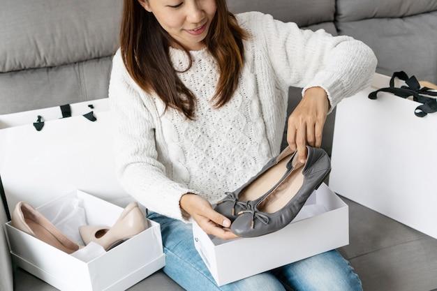 アジアの女性が彼女の新しい靴を見て、自宅のソファに座って、技術、デジタルライフスタイルのデジタルライフスタイル
