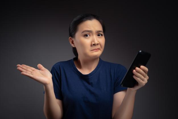 스마트 폰 뉴스를 읽고 혼란스러워하는 아시아 여자.