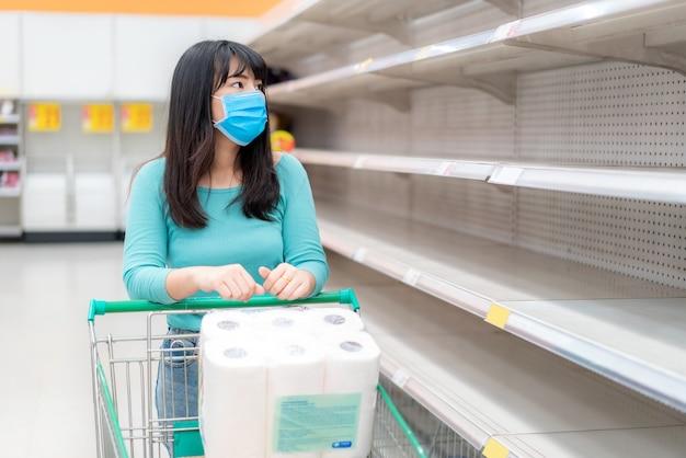 Covid-19コロナウイルスの恐怖の中でスーパーマーケットの空のトイレットペーパーの棚を見ているアジアの女性は、買い物客がパニックの購入とパンデミックの準備をしてトイレットペーパーを備蓄します。