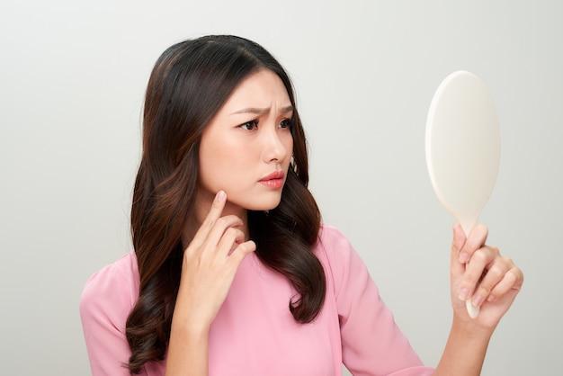 彼女の肌に問題を抱えて鏡を見ているアジアの女性。