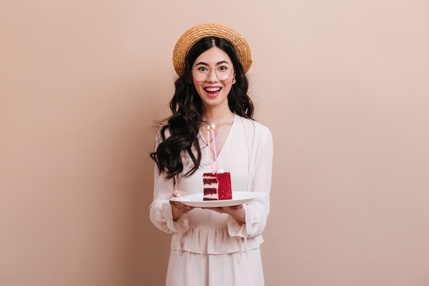 Donna asiatica che guarda l'obbiettivo con il sorriso. felice donna giapponese in cappello di paglia tenendo la torta.