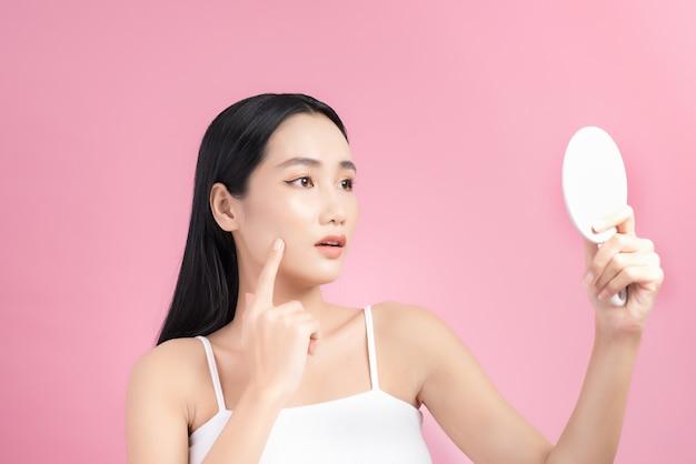 거울을보고 그녀의 피부에 대해 걱정하는 아시아 여자.