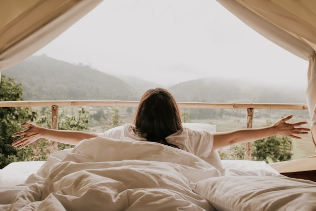 Asian woman looking at mountain view from tent in sunset time