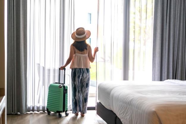 ホテルの部屋で荷物を持って窓の外を見ているアジアの女性。旅行、休日のコンセプト