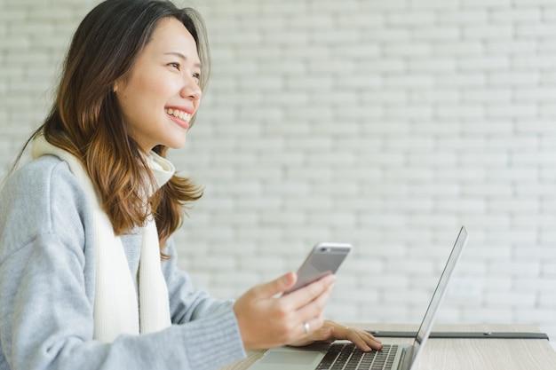 Азиатская женщина смотря снаружи с продырявливать smartphone и использует компьтер-книжку