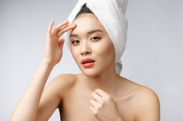 Asian woman looking at pimple on face. young woman try to remove her pimple